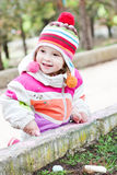 Happy toddler girl sitting with chalk. On the outdoors royalty free stock image