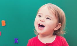 Happy toddler girl smiling in front of a chalkboard Stock Photos
