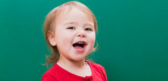 Happy toddler girl smiling in front of a chalkboard Royalty Free Stock Photos
