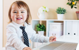 Happy toddler girl smiling while using a laptop Stock Photo