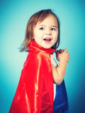 Happy toddler girl in a super hero cape. Happy toddler girl playing in a super hero cape royalty free stock images