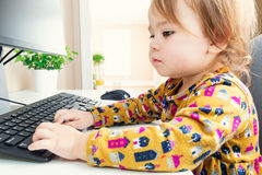 Happy toddler girl typing on her computer keyboard Stock Photo