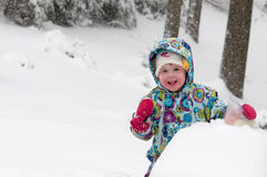 Happy toddler girl in warm coat and knitted hat tossing up snow and having a fun in the winter outside, outdoor portrait Stock Photos