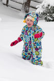Happy toddler girl in warm coat and knitted hat tossing up snow and having a fun in the winter outside, outdoor portrait royalty free stock photography
