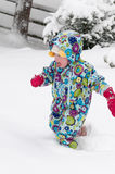 Happy toddler girl in warm coat and knitted hat tossing up snow and having a fun in the winter outside, outdoor portrait Stock Photography