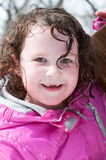 Happy toddler girl in warm coat on on snow day and having a fun in the winter outside, outdoor portrait Royalty Free Stock Image