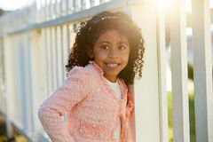 Happy toddler kid girl portrait in a park fence Royalty Free Stock Photos