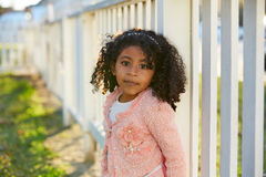 Happy toddler kid girl portrait in a park fence Stock Images