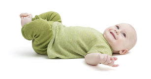 Happy toddler lying on his back in green clothing Stock Photos