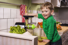 Happy toddler making green juice Royalty Free Stock Photography