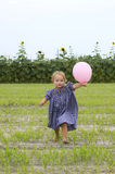 Happy toddler running with balloon Stock Photo