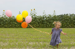 Happy toddler running with balloons in field Royalty Free Stock Image