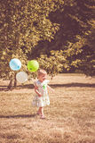 Happy toddler running with balloons. A smiling toddler girl running with balloons in a park Stock Images