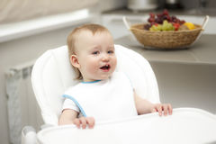 Happy toddler sitting in highchair and eating porridge. Baby lea Stock Image
