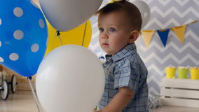 A happy toddler smiles surrounded by balloons. stock video