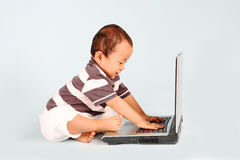 Happy Toddler Using a Laptop. A happy toddler learn how to use a laptop computer Stock Photo