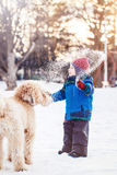 Happy toddler white Caucasian boy running and playing with snow and white large big pet dog Stock Photo