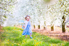 Happy toddlger girl in fairy costume in blooming garden. Adorable toddler girl with curly hair and flower crown wearing a magic fairy costume with a blue dress Stock Photography