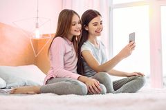 Positive delighted girls taking photo on telephone royalty free stock photo