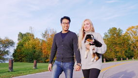 Happy Together with his beloved dog. Multiethnic couple walking in the park with his dog. Caucasian woman carries a. Walk with your favorite puppy. Multiethnic