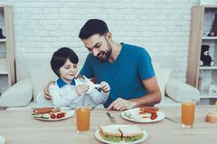 Happy Together. Man. Spends time. Son. Father. Happy Together. Man. Spends time. Son. Father of Boy. Engaged. Raising Child. Father Feeds his Son. Boy. Having stock photo