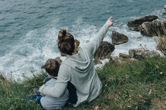 Happy together. Mother and her son raised their hands upwards si. Tting on the mountain above the sea. Freedom concept Stock Photos