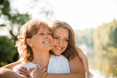 Happy together - mother and teenage daughter outdoor. Mature mother hugging with her teen daughter outdoor in nature on sunny day Royalty Free Stock Photo