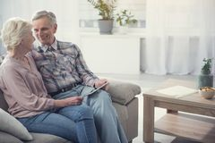 Glad senior couple resting with device. Happy together. Satisfied elderly men and women relaxing on couch with tablet in hands. Copy space in right side Royalty Free Stock Photography