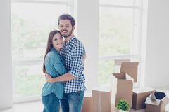 Happy together. What a joy! Young beautiful cuddling married couple bought a new apartment and moved to it, it is light and royalty free stock image