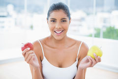 Happy toned brunette holding apples Royalty Free Stock Images