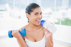 Happy toned brunette holding dumbbells and sports bottle Royalty Free Stock Photo