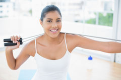 Happy toned brunette sitting on floor with skipping rope Royalty Free Stock Image