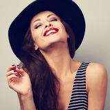 Happy toothy laughing brunette young woman in black hat with clo Royalty Free Stock Image