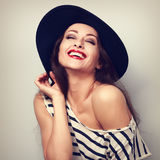 Happy toothy laughing brunette young woman in black hat with clo Stock Images
