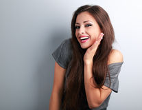 Happy toothy laughing brunette young woman with hand near face  Stock Photography