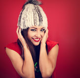 Happy toothy laughing makeup woman in white fur winter hat on re Royalty Free Stock Photography
