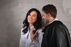 Happy toothy smiling business woman and thinking businessman in white shirts on loft style wall studio background. Love and flirt royalty free stock photos