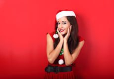 Happy toothy smiling excited woman in santa claus costume with b. Right makeup and red lipstick posing on bright red background Royalty Free Stock Photography