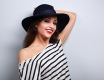 Happy toothy smiling female model in black elegant hat on blue b. Ackground Royalty Free Stock Photo