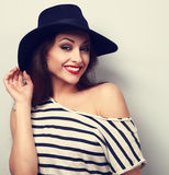 Happy toothy smiling makeup female model in black elegant hat wi. Th red lipstick. Vintage toned portrait Stock Photography