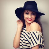 Happy toothy smiling makeup female model in black hat with red l. Ipstick posing. Toned vintage portrait Stock Images