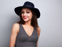 Happy toothy smiling makeup woman in black fashion hat on blue b. Ackground Royalty Free Stock Photo