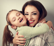 Happy toothy smiling mother cuddling emotional fun kid girl with Royalty Free Stock Images