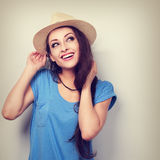 Happy toothy smiling woman in hat thinking and looking up. Toned Royalty Free Stock Photography