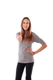 Happy toothy smiling young girl showing thumb up standing over w Stock Image