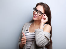 Happy toothy smiling young woman in glasses showing thumb up Royalty Free Stock Photography