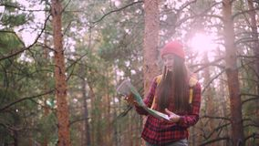 Happy tourist attractive young woman is travelling in forest then looking at map and looking around exploring wood