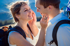 Happy tourist bride and groom stroking face of each other close up. Mountains on background Royalty Free Stock Images