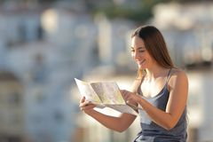 Happy tourist checking map on vacation in a town royalty free stock images