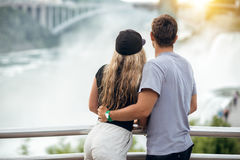 Happy tourist couple enjoying the view to Niagara Falls during romantic vacation. People looking to nature landscape at sunset tim Royalty Free Stock Images